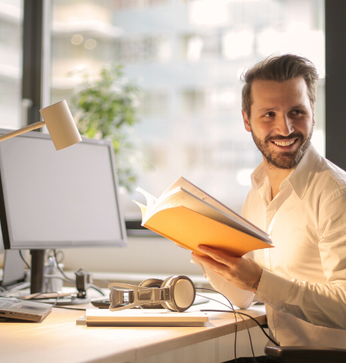 man holding book working in office