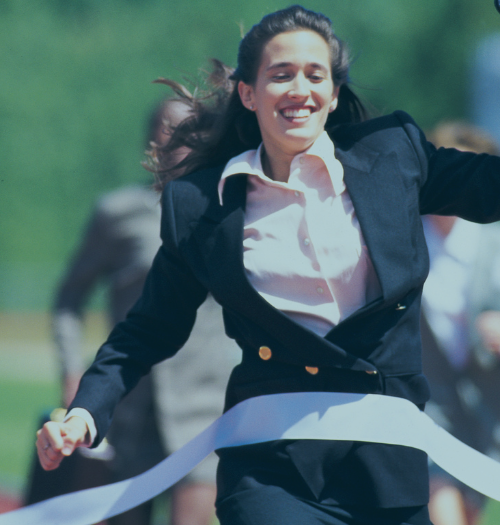 business woman running into finish line